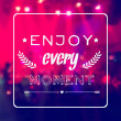 "Vector motivational card ""Enjoy every moment"". Blurred background with rock stage and crowd. — Stock Vector"
