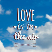 "Vector blurred illustration with clouds, blue sky and text ""Love is in the air"" — Stock Vector"