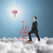 Businessman climbing a ladder — Stock Photo