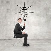 Businessman pointing to bulb — Stockfoto