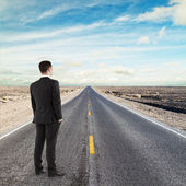 Businessman standing on road — Stockfoto