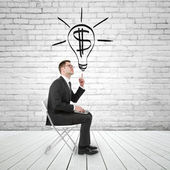 Businessman pointing to lightbulb — Stock Photo