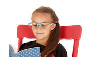 Young girl in trendy blue glasses reading a book — Стоковое фото