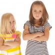 Stock Photo: Two young sisters angry at each other younger one glancing up at