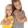 Two sisters standing back to back with arms folded happy — Stockfoto