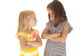Two sisters with arms folded angry looking at each other — Stock Photo