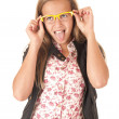 Young female model with yellow glasses sticking her tongue out — Stock Photo