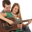 Young couple in love sitting playing guitar — Stock Photo