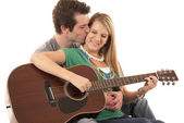 Young couple in love sitting playing guitar kissing — Stock Photo