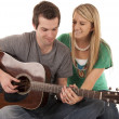 Young couple holding hands playing guitar — Stock Photo