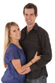 Happy young couple embraced looking at camera — Stock Photo