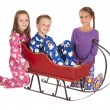 Three children in winter pajamas around a sleigh — Stock Photo