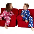 Two children laughing wearing winter pajamas sitting in red chai — Стоковая фотография