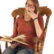 Student in rocking chair yawning while reading a book — Stok fotoğraf