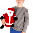 Young boy holding a stuffed santa smiling happily — Stock Photo