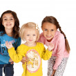 Three cute young girls leaning towards the camera — Stock Photo
