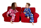 Two children laughing wearing winter pajamas sitting in red chai — Stok fotoğraf