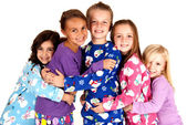 Happy children in winter pajamas hugging each other — Stock Photo