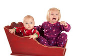 Two toddlers in sleigh one is sad and crying — Stock Photo