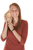 Young woman listening to a seashell smiling — Stock Photo