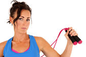 Woman with jump rope and workout clothes looking at camera — Stock fotografie