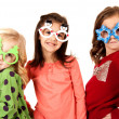 Girls wearing funny glasses with christmas theme — Stock Photo