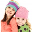 Two adorable girls wearing winter hats hugging — Stock Photo