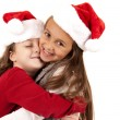 Two young girls wearing santa hats hugging — Φωτογραφία Αρχείου