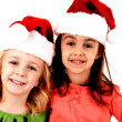 Adorable smiling girls in christmas santa hats — Stock Photo