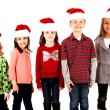 Five kids standing wearing santa hats smiling — Stock Photo