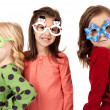Three adorable girls wearing funny winter glasses with fun expre — Stock Photo