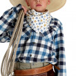 Adorable young cowboy wearing a large cowboy hat holding a rope — Stock Photo