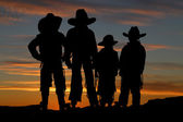 Beautiful silhouette of four young cowboys with a sunset backgro — Stock Photo