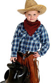 Adorable young cowboy hands on hip holding saddle — Stock Photo