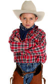 Adorable young cowboy looking at camera arms folded — Stock Photo
