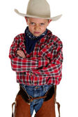 Young cowboy glaring at camera wearing hat and chaps arms folded — Stock Photo