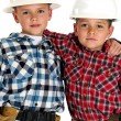 Two young brothers wearing hardhats and tool belts hugging — Stock Photo