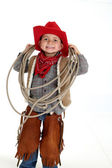 Funny young cowboy with floppy ears smiling holding a rope — Stock Photo