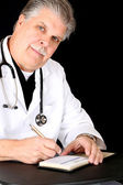 Handsome mature medical doctor writing a script — Stock Photo