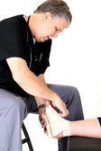 Mature podiatrist in scrubs wrapping a girl' ankle — Stockfoto