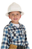 Cute boy in a construction hardhat looking at camera smiling — Stock Photo