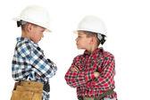 Twee jongens vechten dragen bouw hardhats op zoek taai — Stockfoto