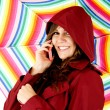 Female model talking on cellphone holding colorful umbrella — Stock Photo #42676999