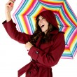 Pretty brunette model taking a selfie picture while holding a rainbow colored umbrella — Stock Photo #42677083