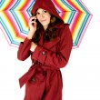 Female model talking on cellphone holding colorful umbrella smiling — Stock Photo