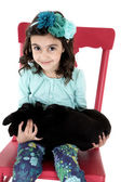 Adorable young girl sitting in chair holding her Labrador puppy — Stock Photo