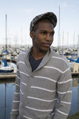 Black male model wearing sweater and newsboy hat at waterfront — Stock Photo