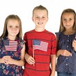 Three cute children holding Ameican flags happy — Stock Photo