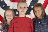 Patriotic children standing in front of a flag banner — Stock Photo