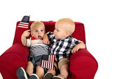 Toddler boys sitting in a red chair holding American flags — Stock Photo